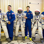 In the Integration Facility at the Baikonur Cosmodrome in Kazakhstan, Expedition 44 crewmembers Kjell Lindgren of NASA (left), Oleg Kononenko of the Russian Federal Space Agency (Roscosmos, center) and Kimiya Yui of the Japan Aerospace Exploration Agency (right) pose with their Sokol launch and entry suits July 11 after a fit check dress rehearsal session. The trio will launch July 23, Kazakh time from Baikonur in their Soyuz TMA-17M spacecraft for a five-month mission on the International Space Station. Credit: Gagarin Cosmonaut Training Center